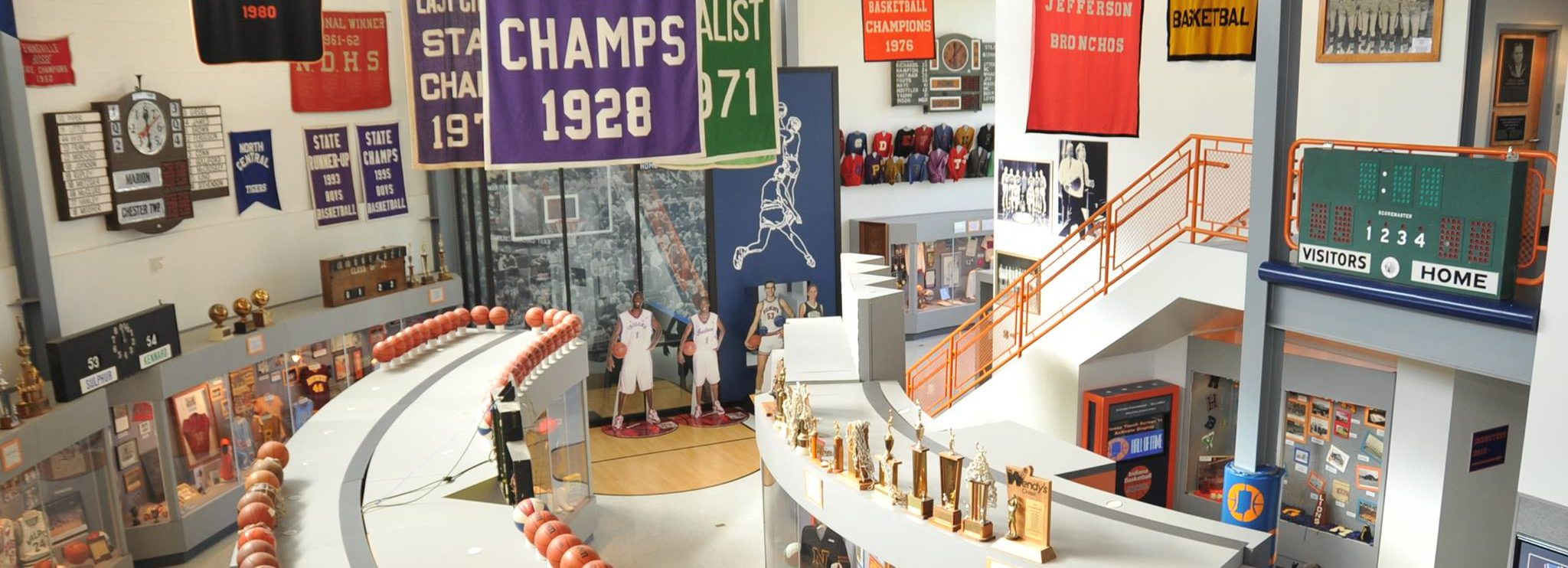 Memorabilia including jerseys, trophies, pendants, and plaques on display at the Indiana Basketball Hall of Fame
